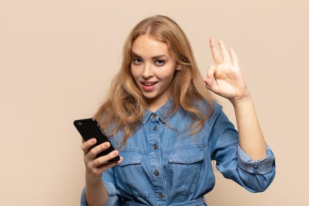 Blonde frau fühlt sich glücklich, entspannt und zufrieden, zeigt zustimmung mit okay geste, lächelnd