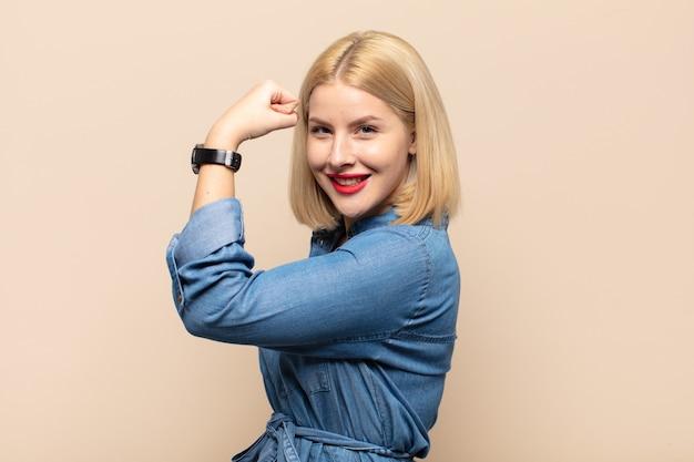 Blonde frau fühlt sich glücklich, zufrieden und kraftvoll, beugt sich fit und muskulöser bizeps und kümmert sich stark um das fitnessstudio