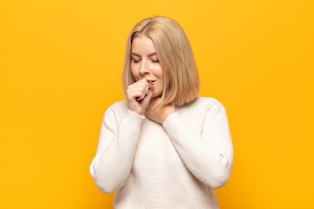 Blonde frau fühlt sich krank mit halsschmerzen und grippesymptomen, husten mit bedecktem mund