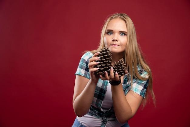 Blonde frau hält eichenkegel in der hand und gibt überraschte posen.