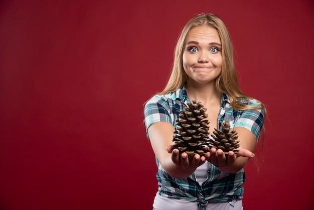 Blonde frau hält eichenkegel in der hand und sieht positiv und fröhlich aus.