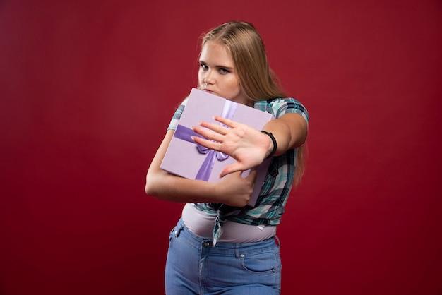 Blonde frau hält eine geschenkbox fest und wird eifersüchtig auf das teilen.