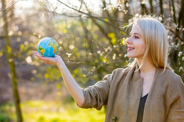 Blonde frau hält erdkugel im blühenden kirschgarten