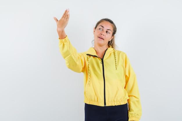 Blonde frau hält hand wie selfie in gelber bomberjacke und schwarzer hose und sieht ernst aus