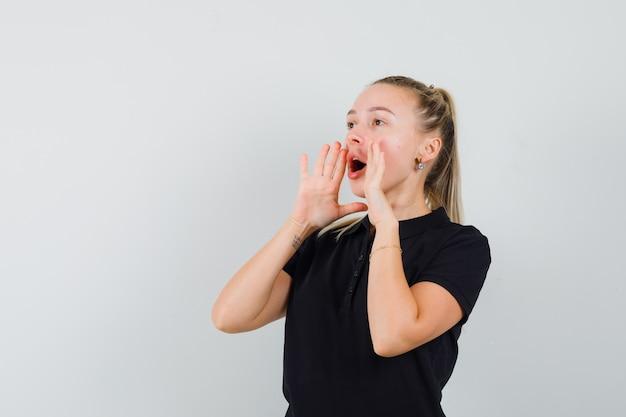 Blonde frau hält ihren mund weit offen, versucht in schwarzem t-shirt zu schreien und sieht glücklich aus