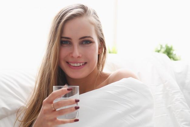 Blonde frau halten glas wasser im arm am frühen morgen im bett bleiben