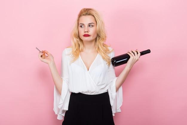 Blonde frau halten weinflasche und korkenzieher