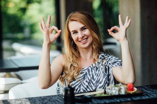 Blonde frau hat eine sushi-zeit im restaurant