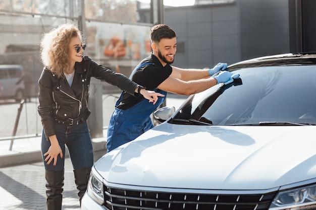 Blonde frau hilft beim waschen ihres autos.