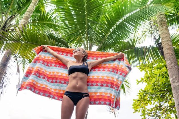 Blonde frau im bikini hält ein buntes tuch vor einer palme