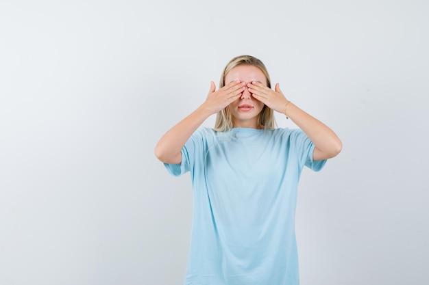 Blonde frau im blauen t-shirt, die die augen mit den händen bedeckt und ernst schaut