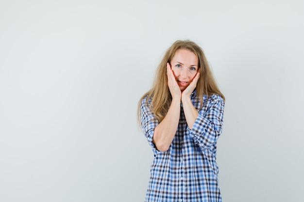 Blonde frau im hemd, das hände auf wangen hält und niedlich schaut,