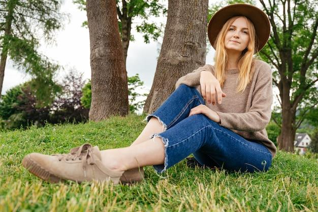 Blonde frau im hut, der im park kühlt. kamera schauen und lächeln. konzept für reisen und aktives leben. draußen