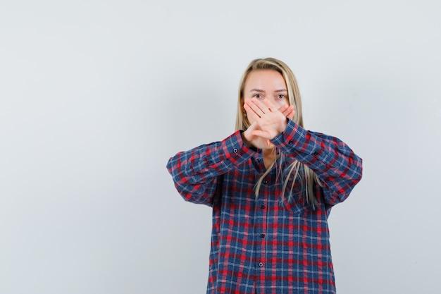 Blonde frau im karierten hemd hält hände gekreuzt und sieht ernst, vorderansicht.