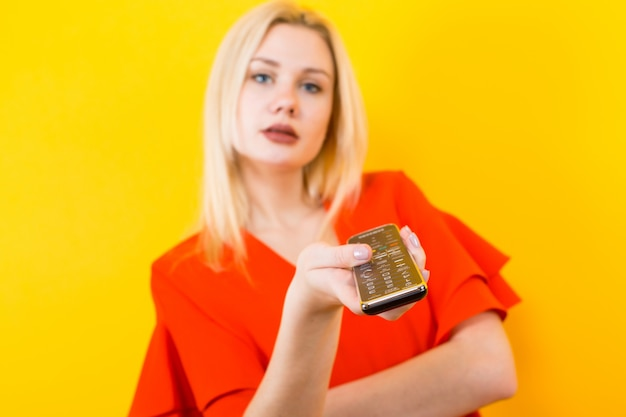 Blonde frau im kleid mit fernbedienung