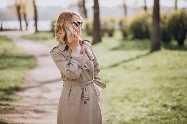 Blonde frau im mantel draußen im park unter verwendung des telefons