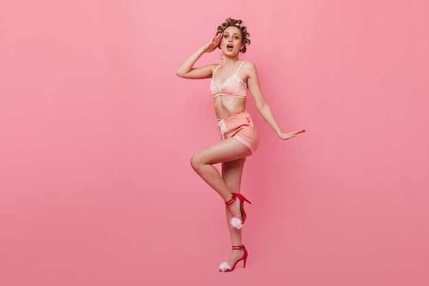Blonde frau im pin-up-pyjama grüßt gegen rosa wand