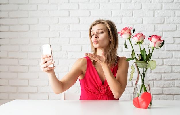Blonde frau im rosa kleid aus online-küssen senden küsse an ihre freunde