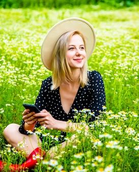 Blonde frau im schwarzen kleid sitzt auf kamille blumenfeld und mit handy