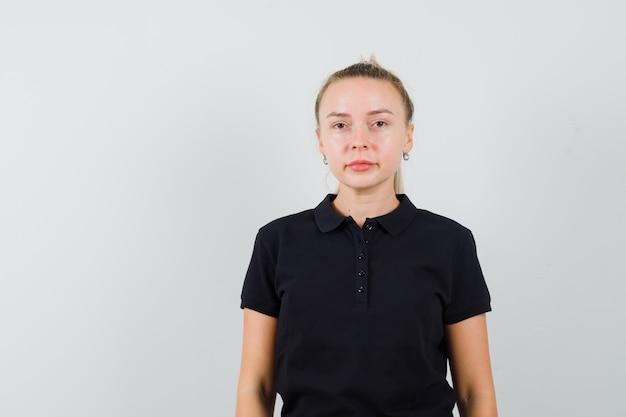 Blonde frau im schwarzen t-shirt, das gerade steht