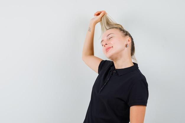 Blonde frau im schwarzen t-shirt, das ihr haar hält und glücklich schaut