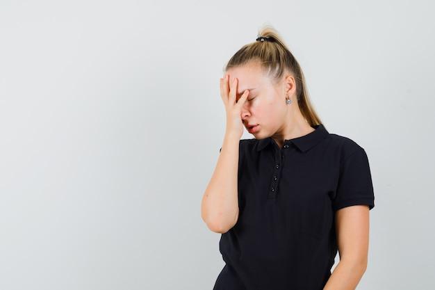 Blonde frau im schwarzen t-shirt, das ihre augen mit den händen bedeckt und müde aussieht