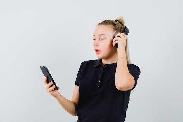 Blonde frau im schwarzen t-shirt, das musik mit kopfhörern hört
