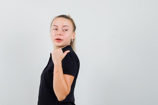 Blonde frau im schwarzen t-shirt, das rückwärts zeigt