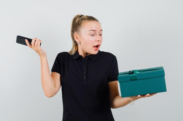 Blonde frau im schwarzen t-shirt hält ihr smartphone in einer hand und schaut auf das geschenk und schaut überrascht