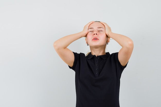 Blonde frau im schwarzen t-shirt hält ihren kopf mit beiden händen und sieht erschöpft aus