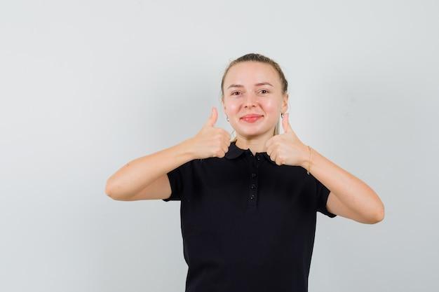 Blonde frau im schwarzen t-shirt zeigt daumen hoch mit ihren beiden händen und lächelt und sieht glücklich aus