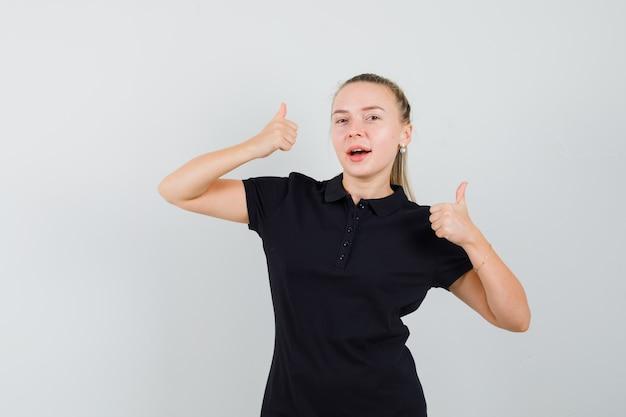 Blonde frau im schwarzen t-shirt zeigt daumen hoch und sieht optimistisch aus