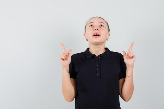 Blonde frau im schwarzen t-shirt zeigt nach oben und schaut nach oben und sieht optimistisch aus