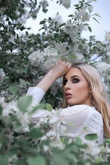 Blonde frau im sommer in den zweigen eines apfelbaums