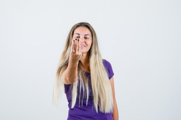Blonde frau im violetten t-shirt, die italienische geste tut und fröhlich, vorderansicht schaut.
