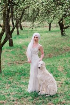 Blonde frau im weißen kleid spielt mit ihrem russischen wolfshundhund im garten