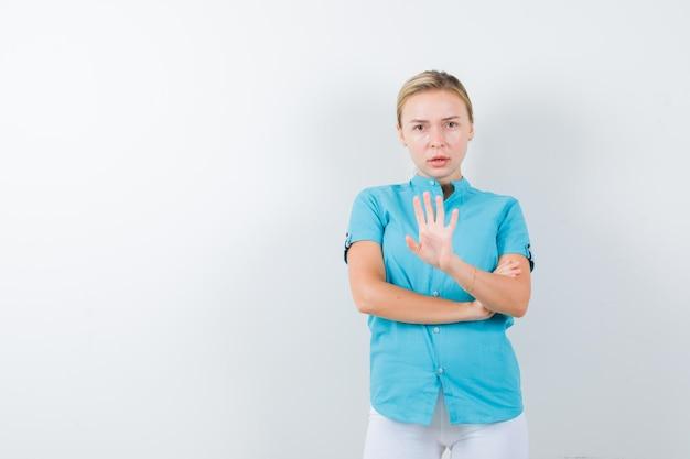 Blonde frau in blauer bluse, die stoppgeste zeigt und selbstbewusst aussieht looking