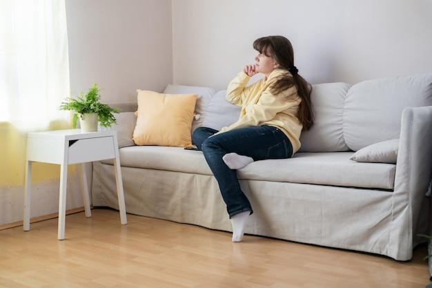 Blonde frau in der gelben bluse, die auf sofa sitzt und fenster betrachtet. selbstpflege, wohlbefinden, mentale helath-konzepte. pastellneutrale farben