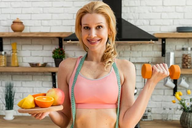 Blonde frau in der küche mit früchten