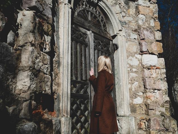 Blonde frau in der nähe von ruinen der alten tür in einem schloss