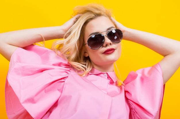 Blonde frau in der rosafarbenen bluse mit sonnenbrillen