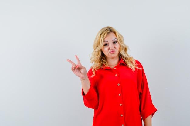 Blonde frau in der roten bluse, die friedenszeichen zeigt und hübsch, vorderansicht schaut.
