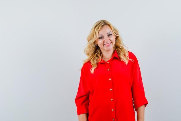 Blonde frau in der roten bluse, die gerade steht und an der kamera aufwirft und glücklich schaut