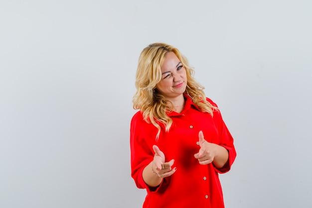 Blonde frau in der roten bluse, die zeigefinger auf kamera zeigt, zwinkert und glücklich schaut