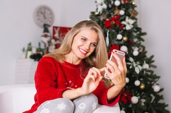 Blonde Frau in der roten Strickjacke, die selfie nimmt