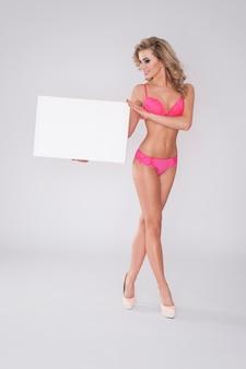 Blonde frau in der sexy unterwäsche, die whiteboard zeigt