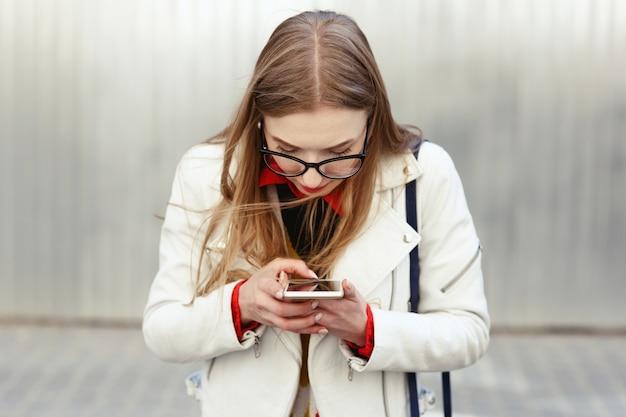 Blonde frau in der weißen jacke macht ein foto an ihrem telefon