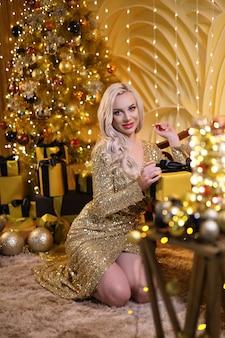 Blonde frau in einem goldenen weihnachtsset