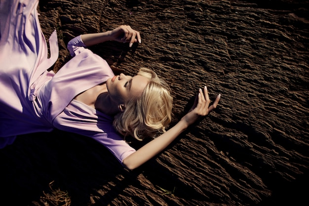 Blonde frau in einem langen rosafarbenen kleid, das auf einem stein liegt