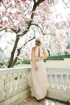 Blonde frau in einem langen weißen kleid